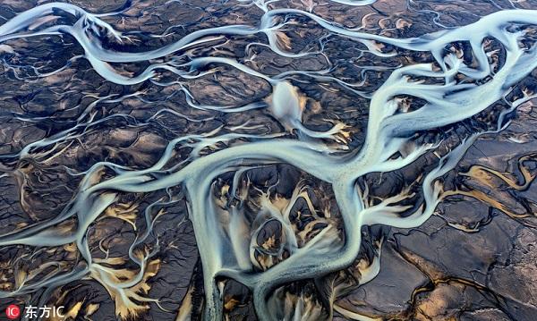 2017年3月16日报道,这些若水彩画般的照片拍摄于冰岛海滨河流三角洲处500米的高空。流水从火山岩与沙石之间穿过进入大海,所到之处形成千沟万壑,沟壑组成美丽的图案,其中一些图案色彩明艳、错综复杂看上去就像是人工画出来的一般。来自莫斯科的摄影师Sergey Aleshchenko拍摄了这些画面。
